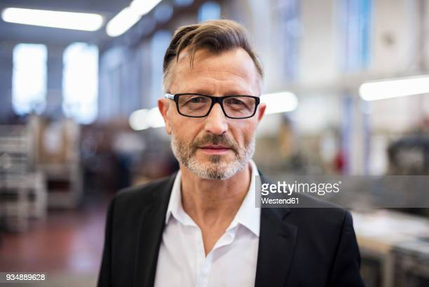 portrait of confident mature businessman in factory - einzelner mann über 40 stock-fotos und bilder