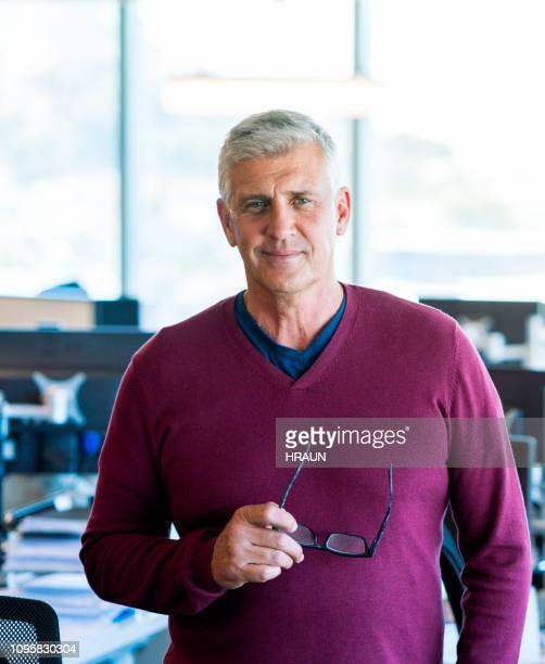 portrait of confident mature businessman in office - maroon stock pictures, royalty-free photos & images