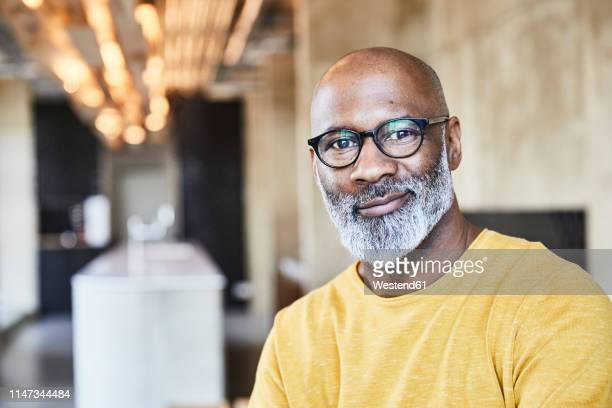 portrait of confident mature businessman in office - mature men stock pictures, royalty-free photos & images