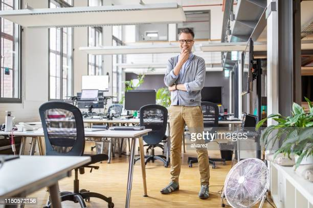 portrait of confident mature businessman in office - standing stock pictures, royalty-free photos & images