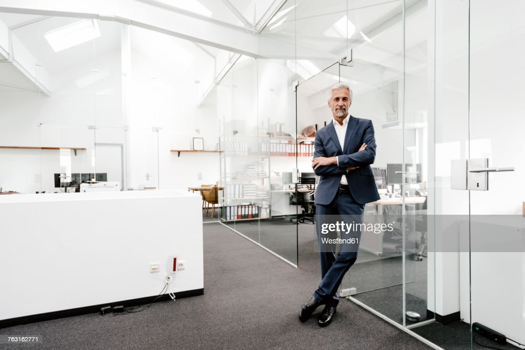 Portrait of confident mature businessman in office : Stock Photo