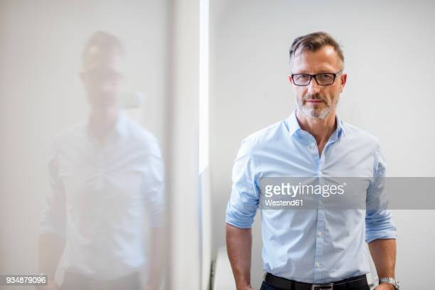 portrait of confident mature businessman in office - mann stock-fotos und bilder