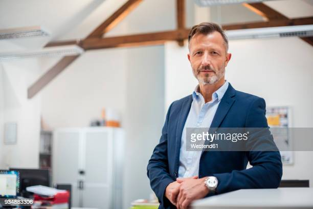 portrait of confident mature businessman in office - anzug stock-fotos und bilder