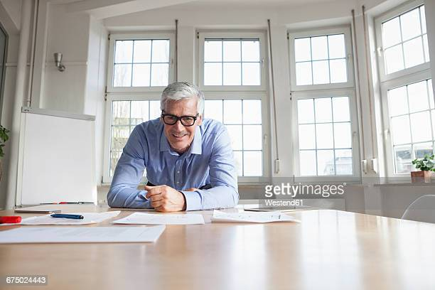 Portrait of confident mature businessman leaning on table in conference room