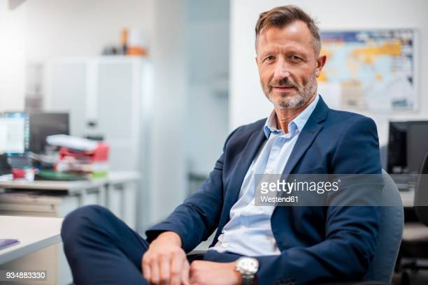 Portrait of confident mature businessman sitting at desk in office