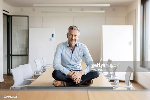 portrait of confident mature businessman sitting on table in conference room - 胡坐 ストックフォトと画像