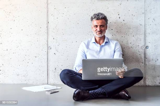 portrait of confident mature businessman sitting on the floor using laptop - cross legged stock pictures, royalty-free photos & images