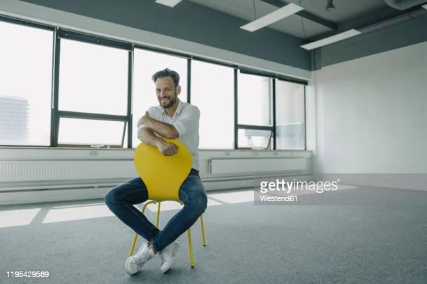 portrait of confident mature businessman sitting on yellow chair in empty office - geschäftsgründung stock-fotos und bilder
