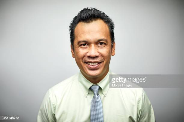 portrait of confident mature businessman smiling - south east asian ethnicity stock pictures, royalty-free photos & images