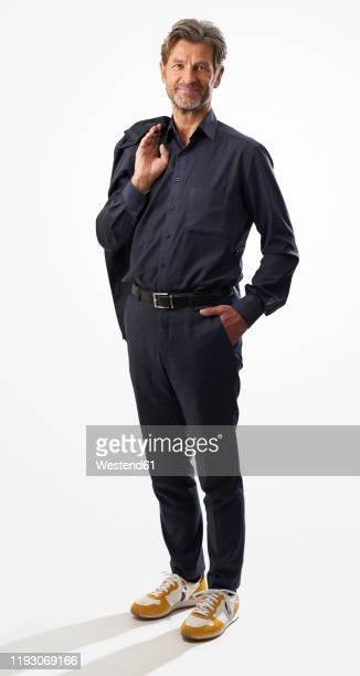 portrait of confident mature businessman standing against light background - standing photos et images de collection