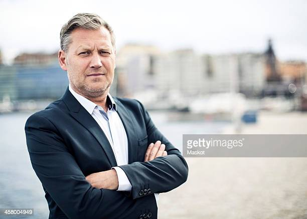 Portrait of confident mature businessman standing arms crossed by sea