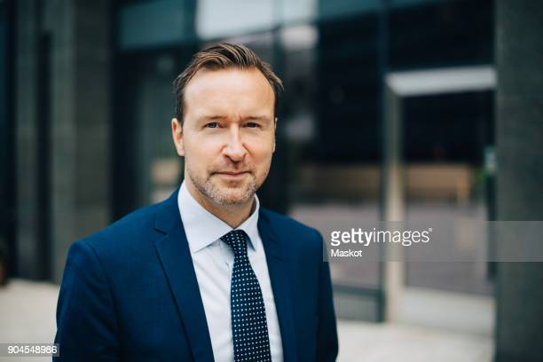 portrait of confident mature businessman standing in city - financiën en economie stockfoto's en -beelden