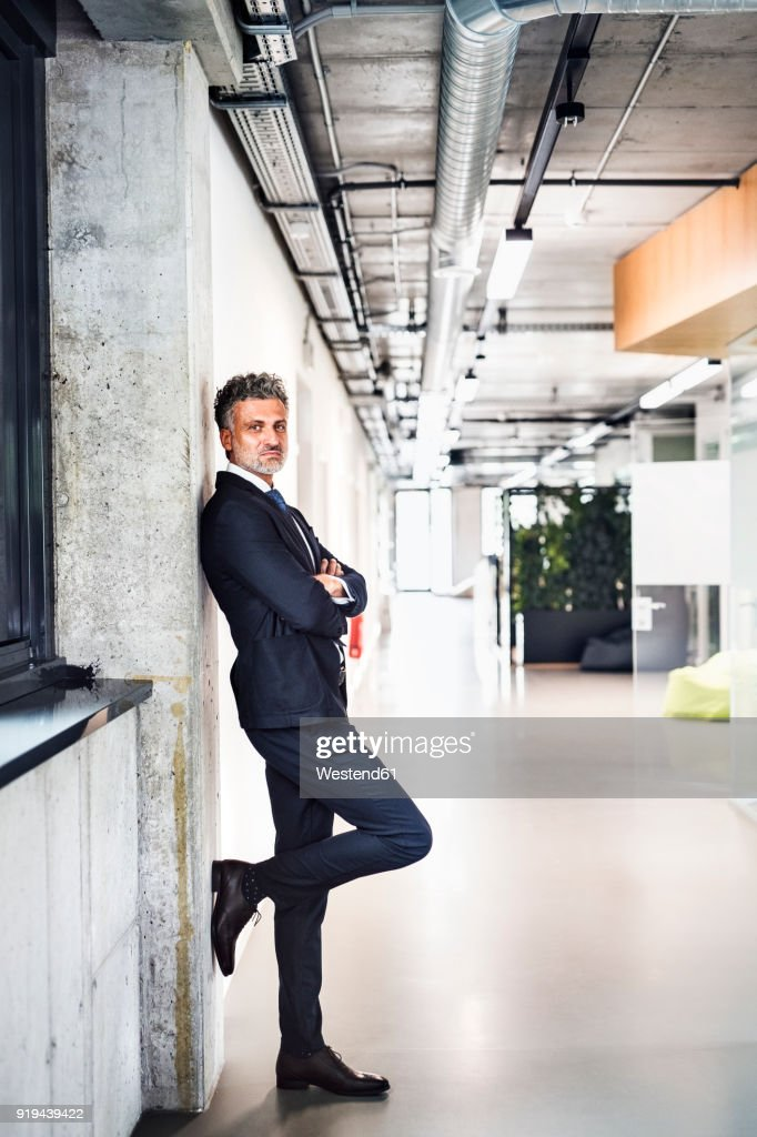 Portrait of confident mature businessman standing in office : Stock Photo