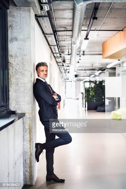 portrait of confident mature businessman standing in office - lehnend stock-fotos und bilder
