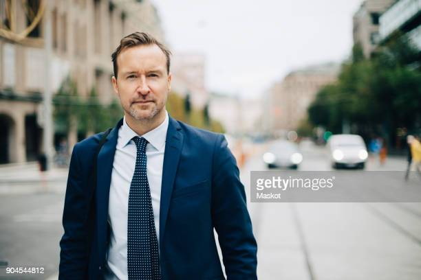 Portrait of confident mature businessman walking on street in city