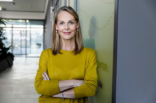 Portrait of confident mature businesswoman in office corridor - gettyimageskorea