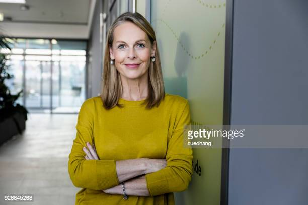 portrait of confident mature businesswoman in office corridor - zakenvrouw stockfoto's en -beelden