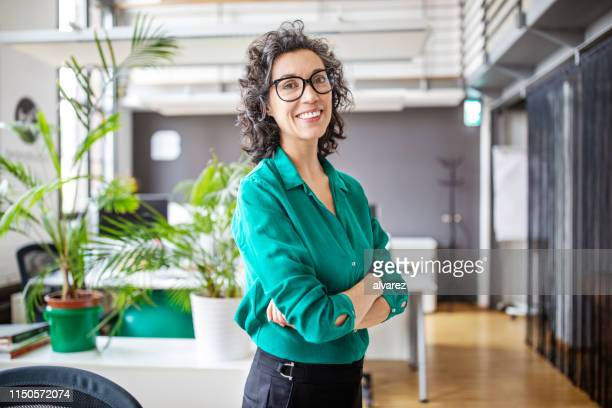 portrait of confident mature businesswoman in office - 40 44 years stock pictures, royalty-free photos & images
