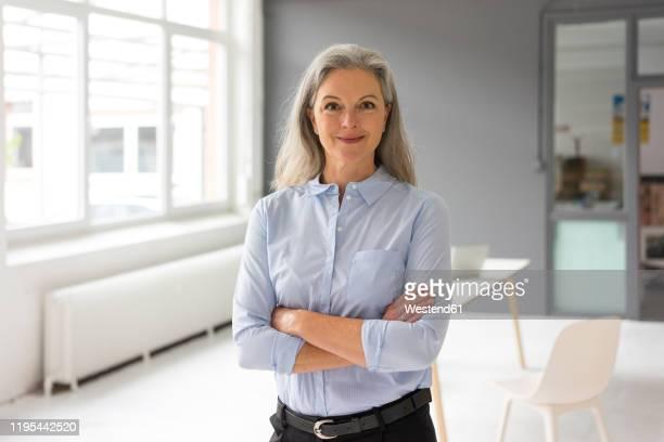 portrait of confident mature businesswoman in office - trabalhadora de colarinho branco imagens e fotografias de stock