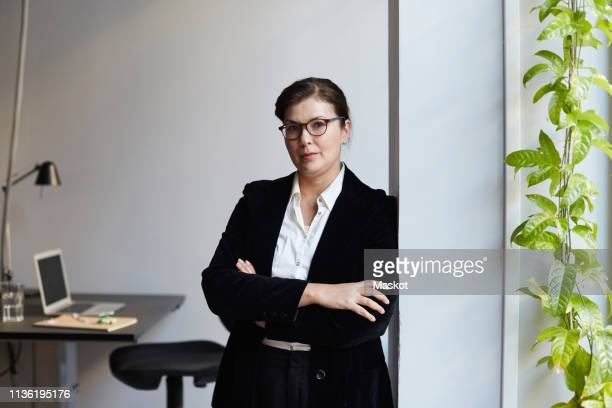 portrait of confident mature businesswoman leaning on wall in office - bank manager stock pictures, royalty-free photos & images
