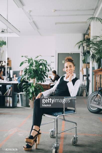 portrait of confident mature businesswoman sitting on chair in office - designberuf stock-fotos und bilder