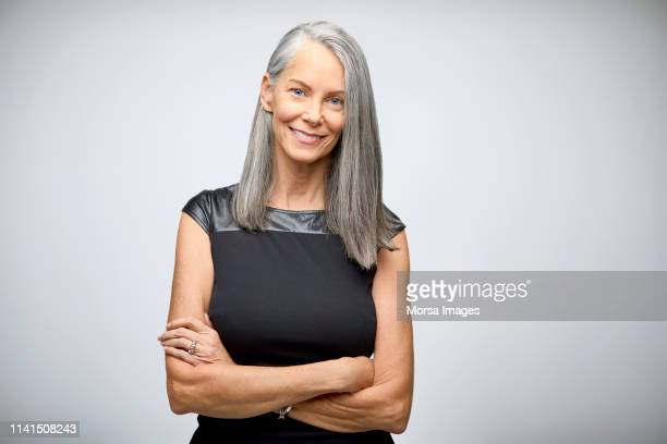 portrait of confident mature businesswoman smiling - bovenlichaam stockfoto's en -beelden