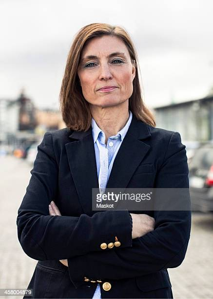 Portrait of confident mature businesswoman standing arms crossed on street