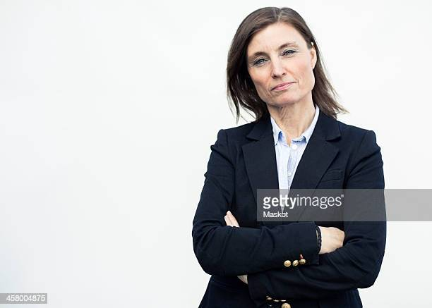 Portrait of confident mature businesswoman standing arms crossed against wall