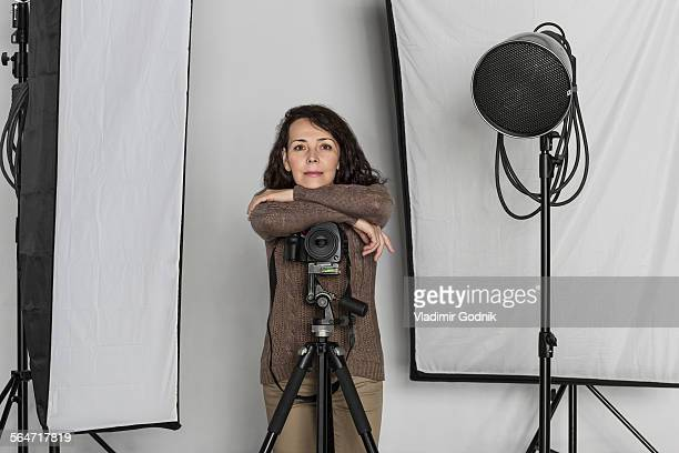 Portrait of confident mature female photographer leaning on camera tripod in photo studio