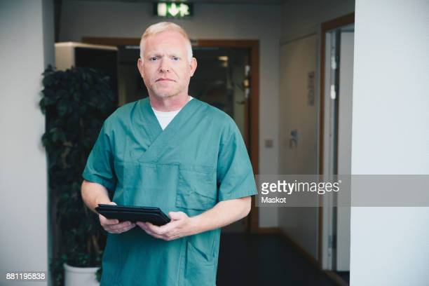Portrait of confident mature male nurse holding digital tablet at hospital corridor
