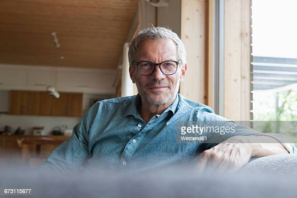 portrait of confident mature man sitting on couch - one mature man only stock pictures, royalty-free photos & images