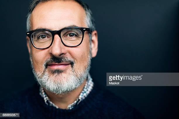 Portrait of confident mature man smiling against gray background
