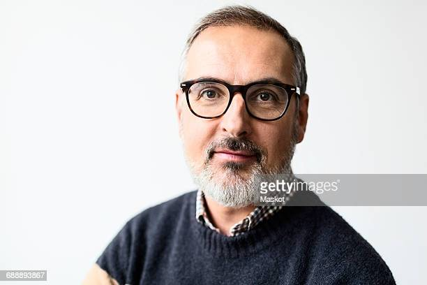 Portrait of confident mature man wearing eyeglasses against white background