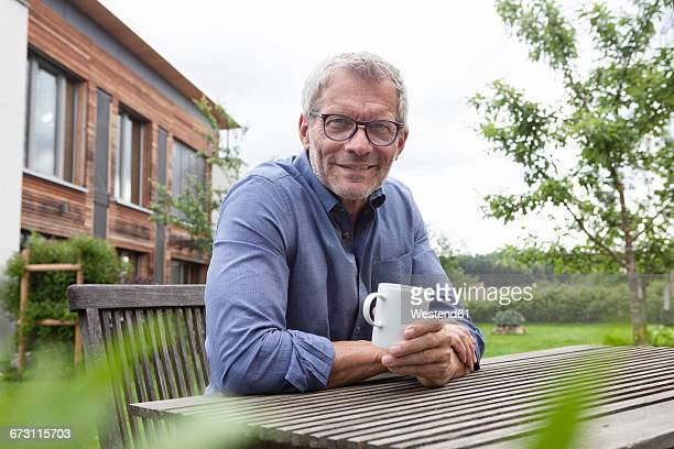 Portrait of confident mature man with cup at garden table