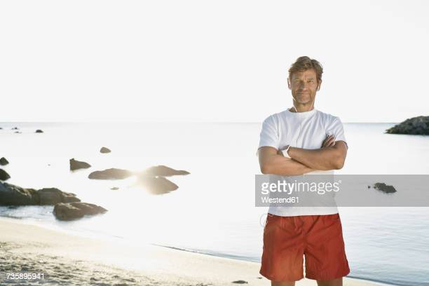 Portrait of confident mature man with earphones and smartwatch on the beach