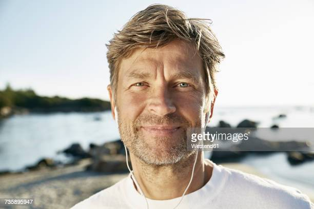 portrait of confident mature man with earphones on the beach - handsome 50 year old men stock photos and pictures