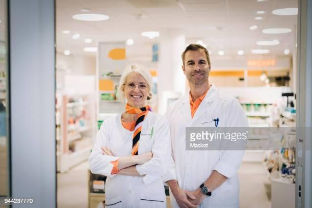 portrait of confident mature owners standing at pharmacy store doorway - vão de porta - fotografias e filmes do acervo