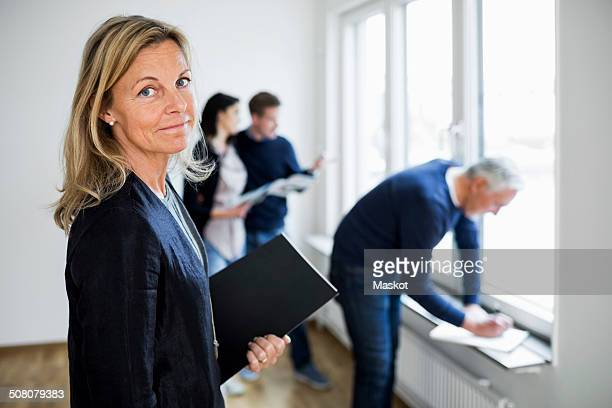 Portrait of confident mature real estate agent with colleague and couple at home