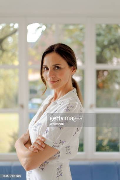 portrait of confident mature woman at home - haar naar achteren stockfoto's en -beelden