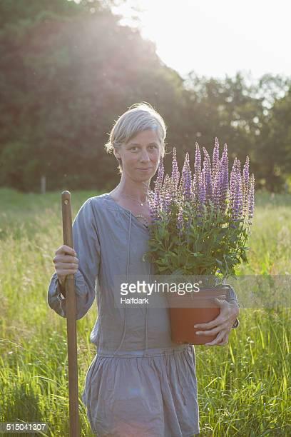 Portrait of confident mature woman holding flower pot at garden