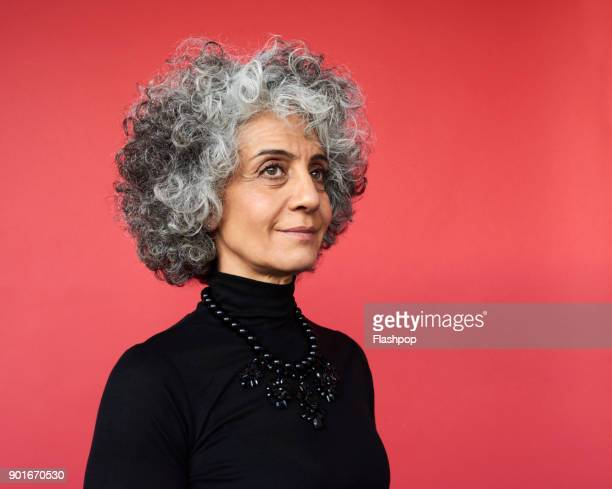 portrait of confident mature woman - wegkijken stockfoto's en -beelden