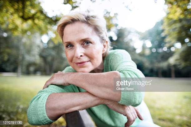 portrait of confident mature woman sitting on a park bench - 50 54 years stock pictures, royalty-free photos & images
