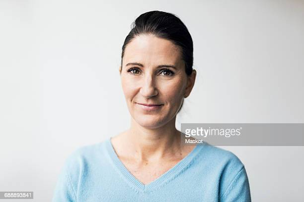 portrait of confident mature woman smiling against white background - haar naar achteren stockfoto's en -beelden