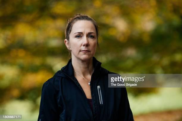 portrait of confident mature woman standing outdoors - white pants fotografías e imágenes de stock