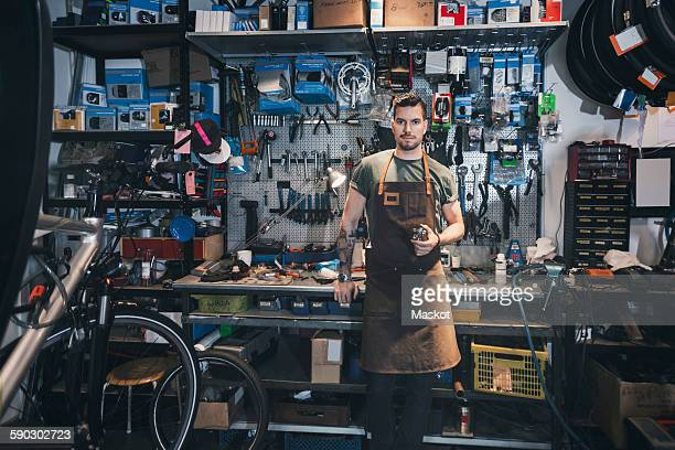 Portrait of confident mechanic at workbench