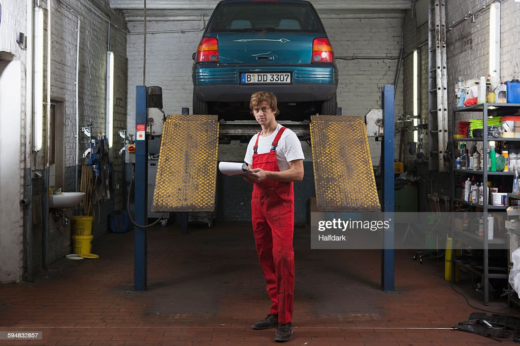 Portrait of confident mechanic holding clipboard at garage : Stock Photo