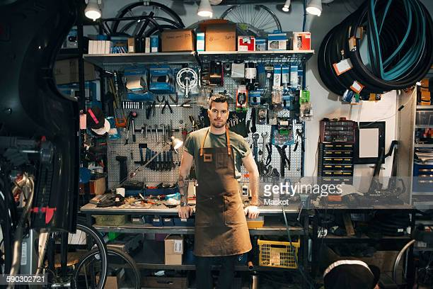 Portrait of confident mechanic leaning on workbench