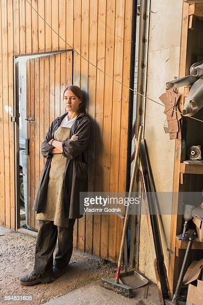 Portrait of confident mechanic with arms crossed leaning on wooden wall at garage
