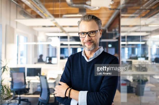 portrait of confident mid adult businessman - korsade armar bildbanksfoton och bilder