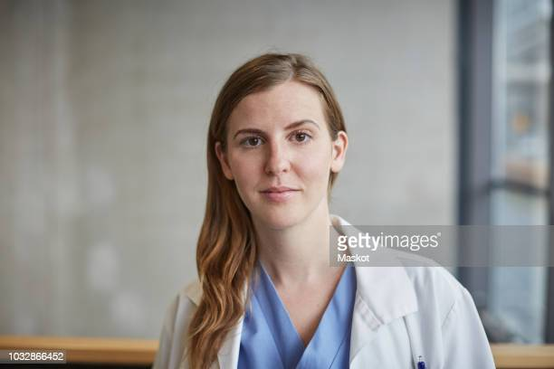 portrait of confident mid adult female doctor standing in corridor at hospital - medical building stock photos and pictures